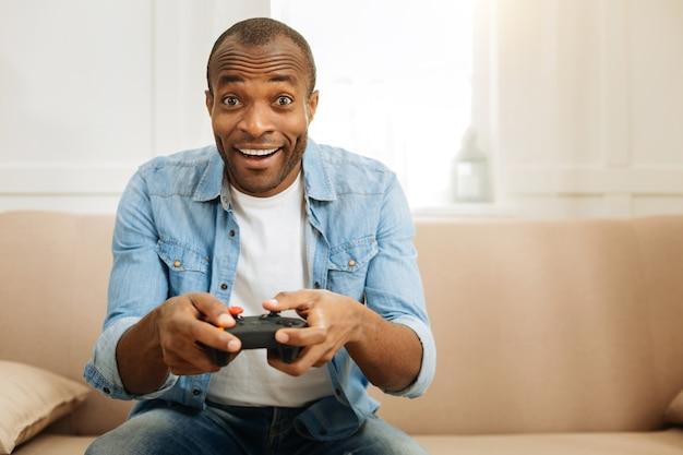 Relaxante. homem afro-americano exuberante e atraente, sorrindo e jogando um jogo com o controle remoto enquanto está sentado no sofá