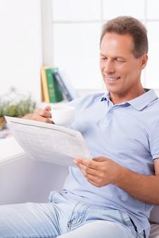 Relaxar com um café fresco e as últimas notícias. homem maduro e alegre bebendo café e lendo jornal enquanto está sentado no sofá em casa