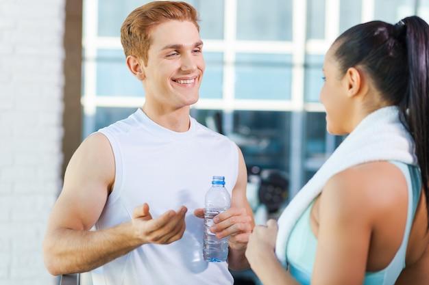 Relaxar depois do treino. lindo casal jovem e esportivo conversando e sorrindo enquanto está de pé na academia