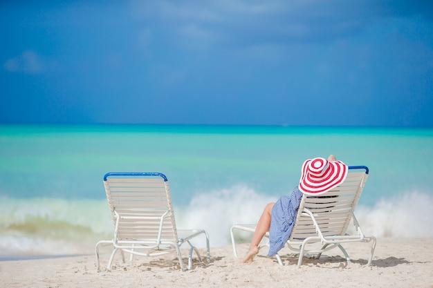 Relaxar e desfrutar de férias de verão, mulher deitada na espreguiçadeira na praia