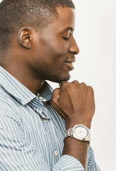 Relaxar empresário afro-americano mostra seu relógio de pulso. retrato do perfil do empresário de pele escura, fechando os olhos e sorrindo com o relógio na mão.