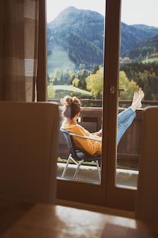 Relaxar. menina sentada em uma cadeira em uma varanda com vista para a montanha