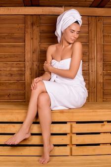Relaxar na sauna. mulher jovem e atraente enrolada em uma toalha, passando um tempo na sauna e mantendo os olhos fechados