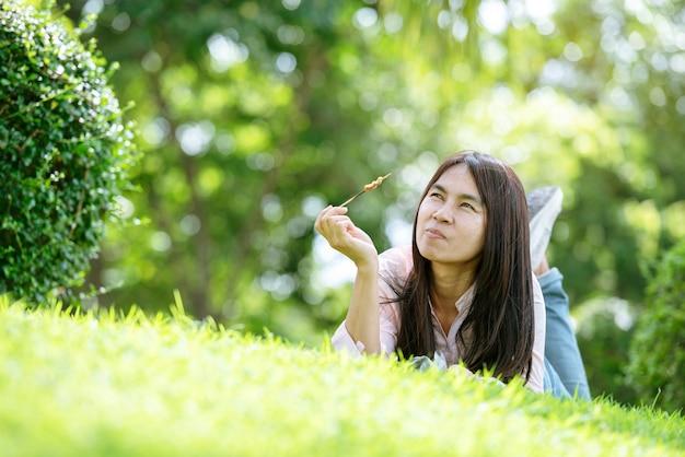 Relaxe a linda mulher asiática com rosto sorridente, deitada em um campo de grama verde em um parque com jardim ao ar livre