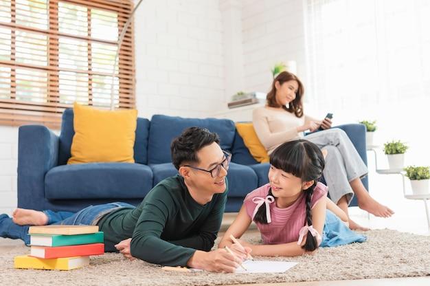 Relaxe a mãe asiática lendo um livro no sofá e o pai com a filha, pintando arte na sala de estar em casa.