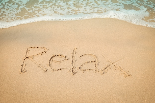Relaxe a mão da mensagem que escreve na praia da areia