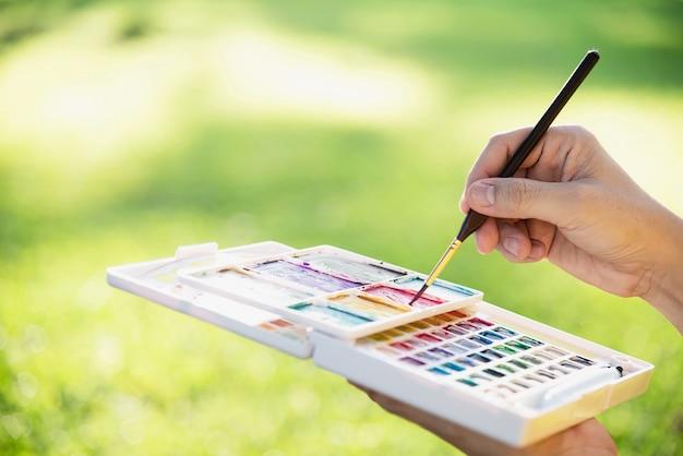Relaxe a mulher pintando o trabalho de arte em aquarela na natureza da floresta de jardim verde