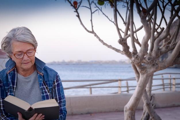 Relaxe e a aposentadoria para uma mulher sênior, apreciando o pôr do sol, lendo um livro sentado perto da praia e comendo uma maçã. horizonte sobre a água.