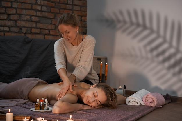 Relaxe e aproveite no salão spa, recebendo massagem por massagista profissional. mulher deitada com as costas nuas relaxando no cobertor do chão