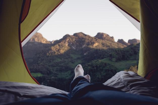 Relaxe, mulher, deitando-se, e, cruze perna, ligado, cobertor, em, barraca, e, olhar, montanha, vista