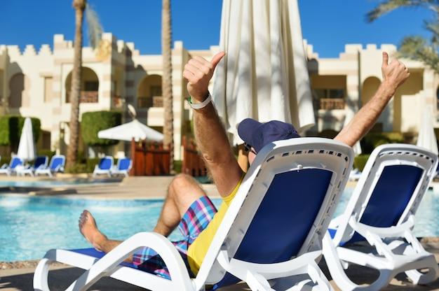 Relaxe na piscina de verão. homem jovem e bem sucedido, deitado numa espreguiçadeira e levantando os braços