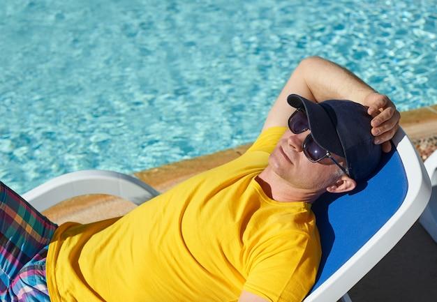 Relaxe na piscina de verão. homem jovem e bem sucedido, deitado numa espreguiçadeira em óculos de sol pretos