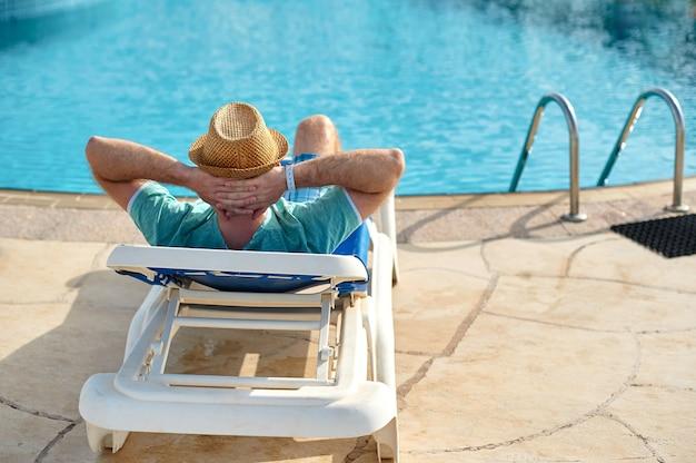 Relaxe na piscina de verão. homem jovem e bem sucedido deitado numa espreguiçadeira no hotel. Foto Premium