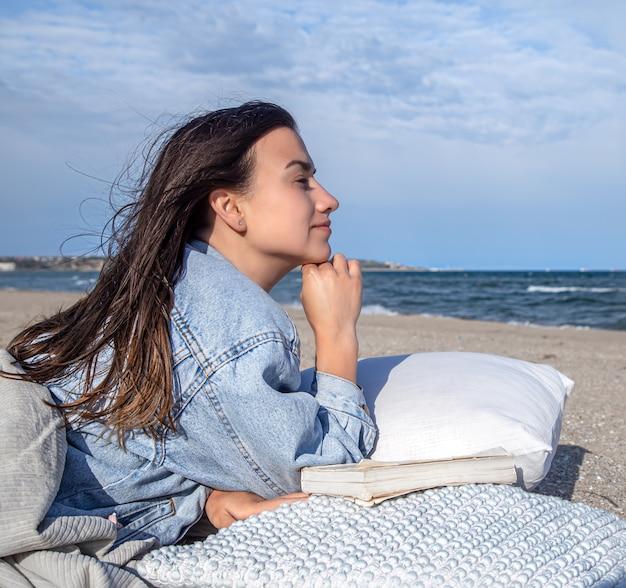 Relaxe o conceito, uma mulher na praia em um clima ventoso, descansando sobre um travesseiro com um livro.