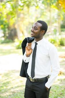 Relaxe o homem de negócios africano retira o terno com o natural verde.