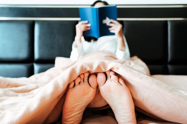 Relaxe pé da mulher sentada na cama lendo o livro