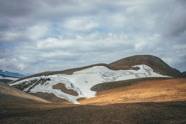 Relevo do deserto da montanha ensolarada com geleira na luz do sol sob céu nublado. paisagem cênica das terras altas com uma pequena geleira no alto de montanhas nas colinas. cenário de montanha minimalista do deserto das terras altas.