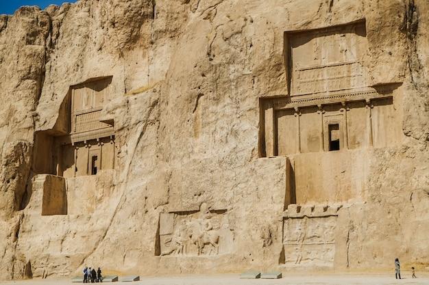 Relevos rupestres iranianos antigos naqsh-e rustam mostram grandes tumbas cortadas no alto da face do penhasco