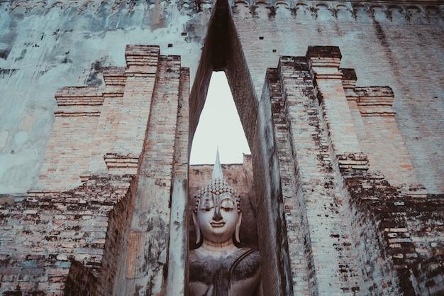 Religião budista, arte antiga e cultura asiática. escultura que senta a imagem de buddha de wat tra phang thong lang no parque nacional de sukhothai em tailândia.