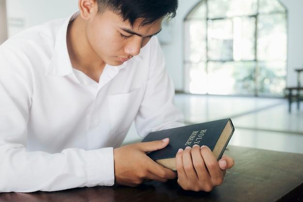 Religião, cristianismo, oração. homem orando, as mãos postas na bíblia.