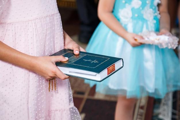 Religião ortodoxa. menina com as mãos na bíblia.
