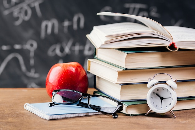 Relógio à frente dos livros didáticos na mesa do professor