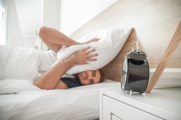 Relógio alarmante e jovem cobrindo a cabeça com um travesseiro enquanto tentava dormir na cama