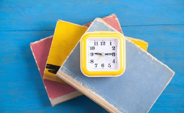 Relógio amarelo e livros na mesa de madeira azul.