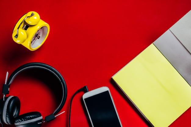 Relógio amarelo, fones de ouvido pretos, cadernos abertos
