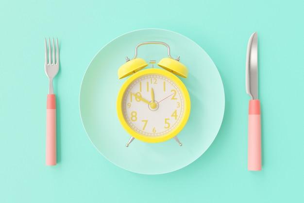 Relógio amarelo no prato azul esverdeado.