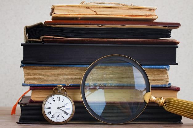 Relógio antigo com lupa na pilha de fundo de livros antigos