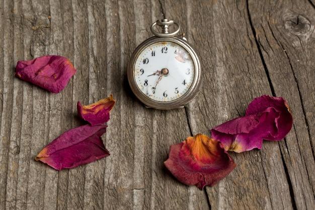 Relógio antigo com pétalas de rosa