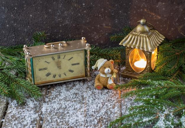 Relógio antigo com uma vela e um urso de brinquedo