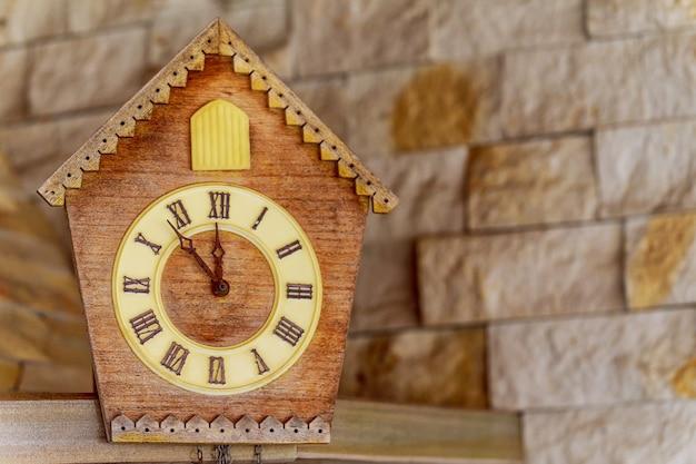 Relógio antigo em uma parede de madeira clara. relógio vintage. relógio de cuco. cópia-espaço.