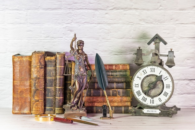 Relógio antigo junto com livros antigos e estatueta da deusa da justiça. temis.