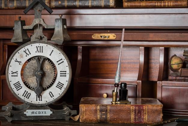 Relógio antigo na estante com livros antigos e caneta