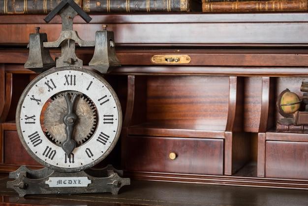 Relógio antigo na estante com livros antigos