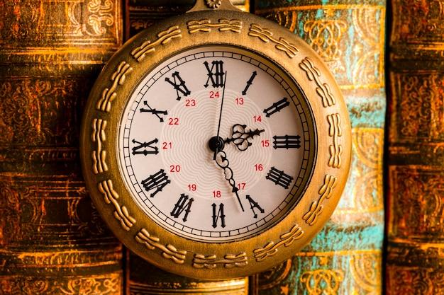 Relógio antigo no fundo de livros antigos.
