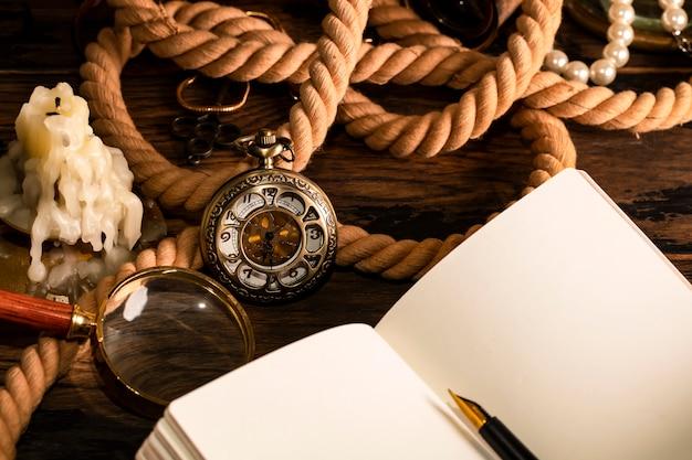Relógio antigo no fundo do caderno vintage e caneta. folha em branco para escrever texto.