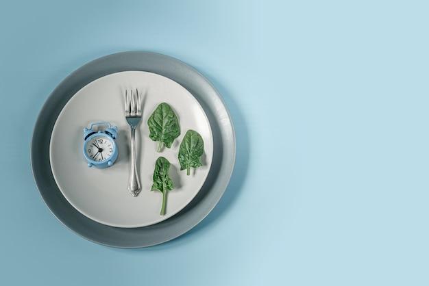 Relógio azul, garfo e folhas de espinafre em prato cinza, dieta de jejum intermitente