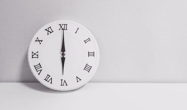 Relógio branco closeup para decorar em 6 horas na mesa de madeira em tom preto e branco
