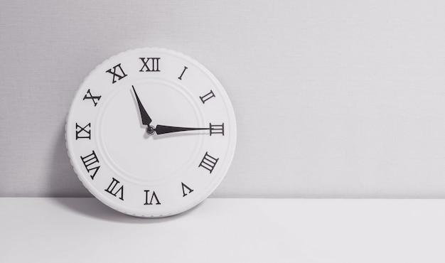 Relógio branco closeup para decorar mostrar um quarto e meia onze horas ou 11:15