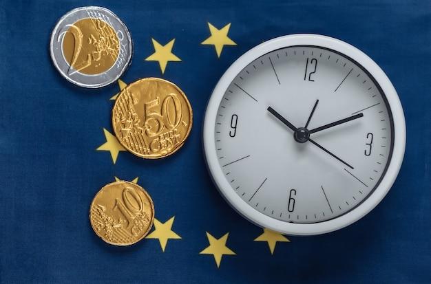 Relógio branco com moedas na bandeira da união europeia
