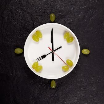 Relógio branco com talheres e uvas em um fundo preto