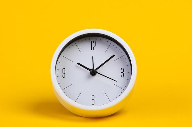 Relógio branco em estúdio amarelo