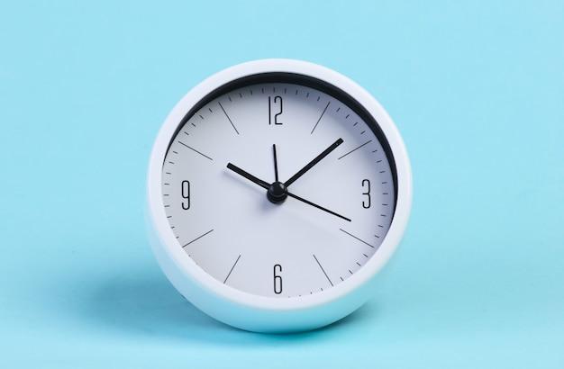 Relógio branco em um estúdio azul
