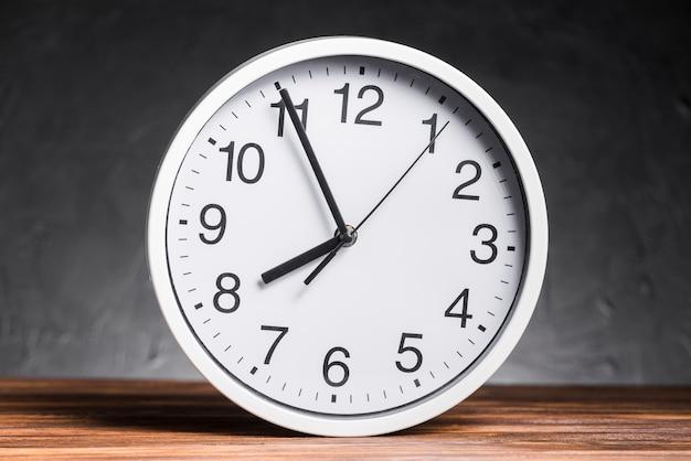 Relógio branco na mesa de madeira contra o fundo preto