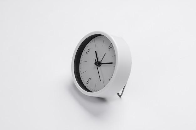 Relógio branco na superfície branca. tiro de estúdio minimalista.