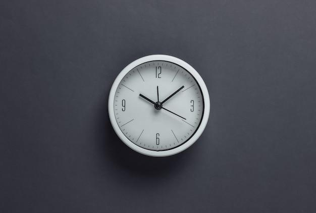 Relógio branco na superfície cinza. o tempo está fugindo. vista do topo