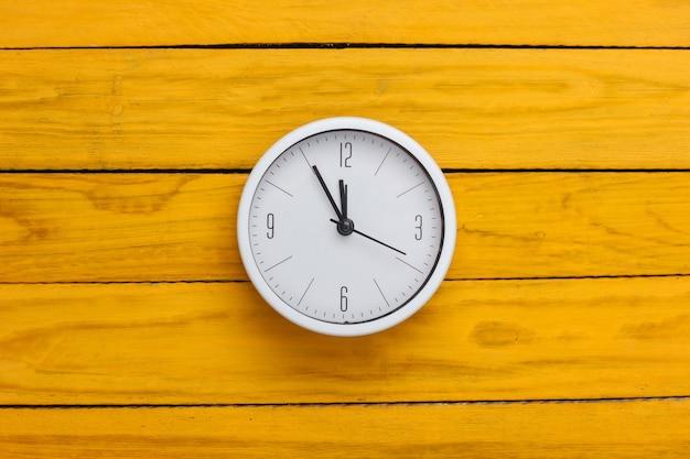 Relógio branco na superfície de madeira amarela. o tempo está fugindo. vista do topo